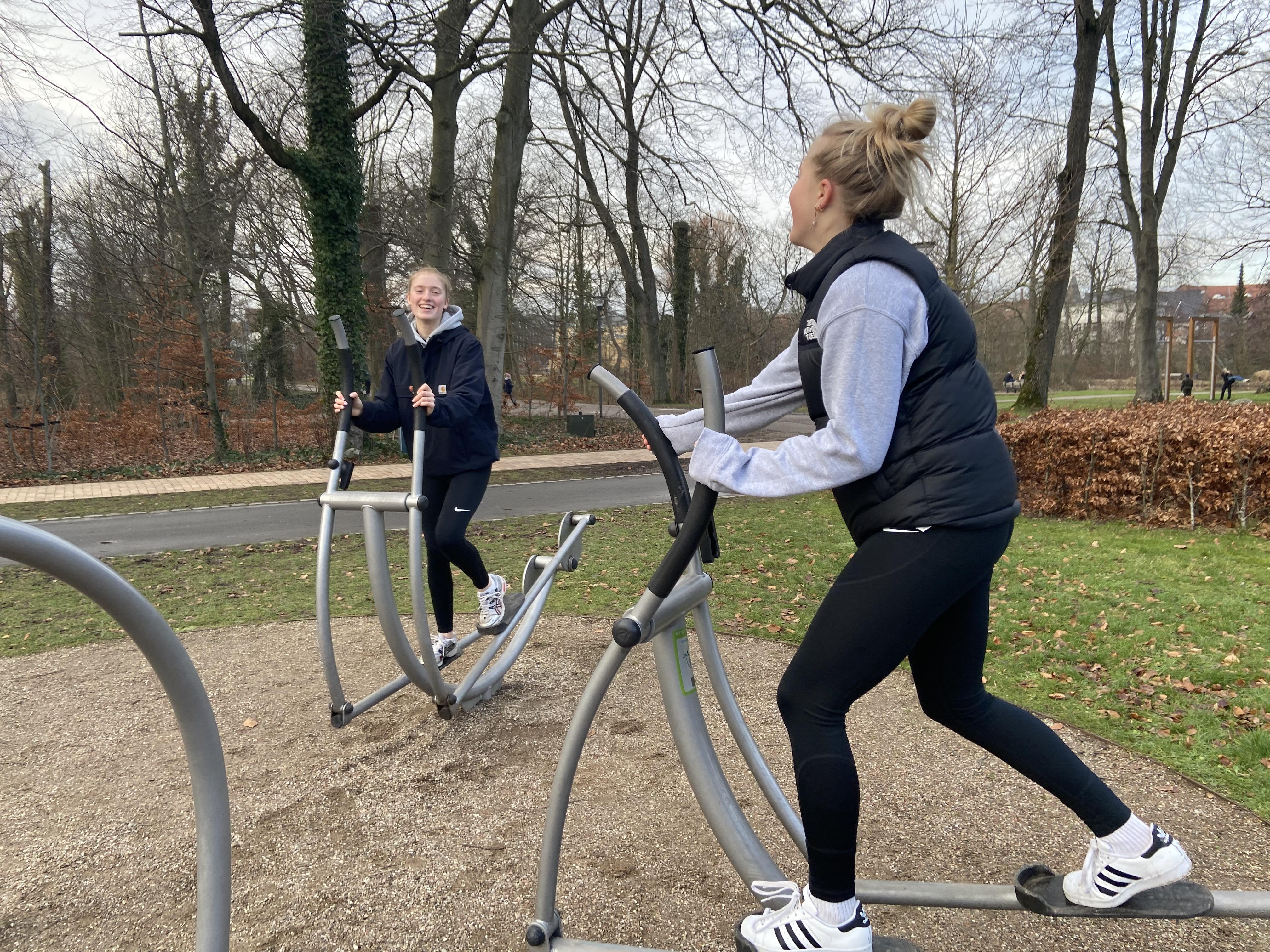 Billede af piger, der bruger udendørs fitness-masksiner